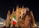 Woman with Italian flag in front of Duomo in evening, Milan