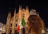 Seen from behind woman with Italian flag near Duomo in evening
