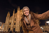 Smiling young woman taking selfie in front of Duomo in evening