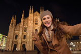 Woman showing victory gesture and taking selfie near Duomo