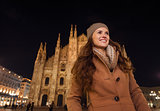 Portrait of happy young woman in the front of Duomo in evening