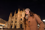 Young woman in front of Duomo in evening looking into distance