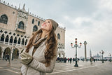 Happy woman sightseeing on St. Mark's Square near Dogi Palace