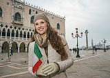 Woman tourist with Italian flag standing on St. Mark's Square