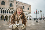 Woman tourist writing sms while standing on St. Mark's Square
