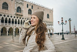 Smiling woman tourist talking cell phone on St. Mark's Square