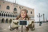 Woman tourist taking selfie with cell phone on St.Mark's Square