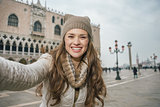 Woman tourist taking selfie on St.Mark's Square near Dogi Palace