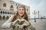 Woman tourist showing heart shaped hands on St. Mark's Square