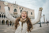 Happy young woman tourist rejoicing on St. Mark's Square, Venice