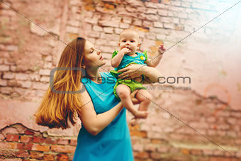Cute Toddler Baby sitting on Mom`s Hands