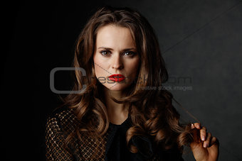 Portrait of woman with long wavy brown hair and red lips