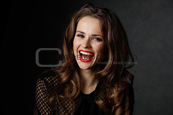 Portrait of smiling woman with long wavy brown hair and red lips