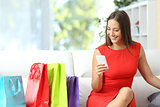 Woman in red buying with a smart phone