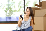 Woman moving home texting in a smart phone