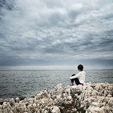 Lonely Woman Sitting at Stormy Sea