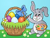 Bunny painting eggs in basket