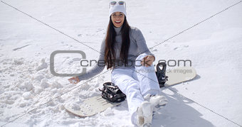 Attractive young woman sitting on her snowboard