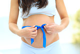 woman holds her baby bump, tied with a blue bow