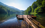 Calm lake water with reflections of forest on the hills and beautiful old wooden pier