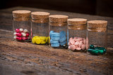 Various pills and capsules in glass containers with caps