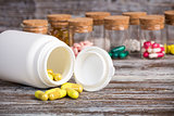 Yellow pills in front of plastic container