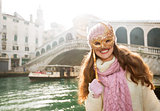 Smiling woman hiding behind Venice Mask near Rialto Bridge