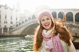 Smiling woman holding Venice Mask in the front of Rialto Bridge