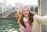 Smiling woman with Venice Mask near Rialto Bridge taking selfie