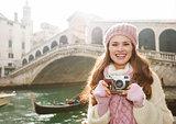 Young woman tourist with retro photo camera near Rialto Bridge