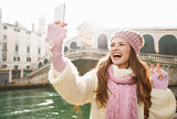 Woman tourist showing victory while taking selfie in Venice