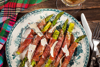 Green asparagus wrapped in parma ham on plate