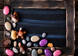 Blackboard decorated with sea objects shaped candies and pebbles