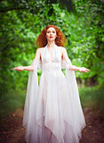 Beautiful redhead woman wearing white dress in a forest