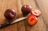 Whole and cut plums with knife on table