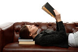 young woman lying on the couch with books under his head