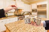 Handing Over Cash for Keys Inside Beautiful Kitchen