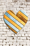 Wooden heart on old brick wall