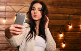 Portrait of a beautiful brunette taking a selfie with her smart phone at home