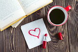 Mug of coffee books and red heart on the napkin on the wooden table