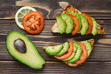 Fresh healthy snacks with avocado, tomato and bread.