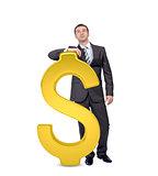 Businessman near big dollar sign