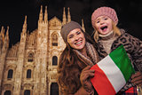 Mother and daughter showing Italian flag near Duomo in Milan