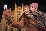 Mother and daughter taking selfie with smartphone in Milan