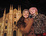 Mother and daughter talking smartphone near Duomo in Milan