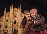 Mother and daughter looking on photos in camera near Duomo