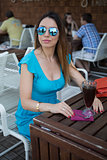 young woman in a blue summer dress at the bar