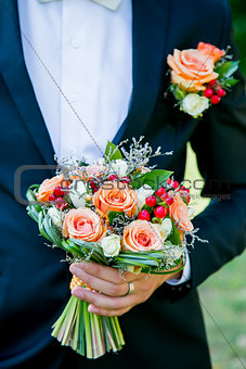 Groom holds a wedding flowers bouquet