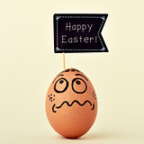egg with a funny face with a signboard with the text happy easte