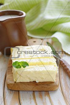 block of fresh organic butter on a wooden board